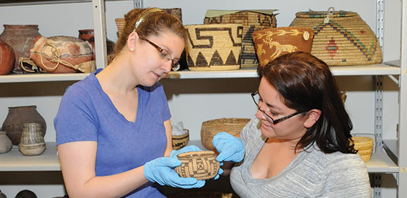 Individuals observing a piece of Southern Colorado artwork from CSU-Pueblo's University Archives and Special Collections