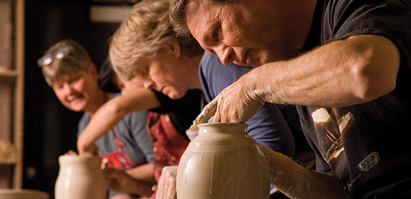 A group of individuals working on pottery.