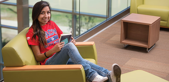 A Colorado State University-Pueblo student reading a book in the General Classroom Building
