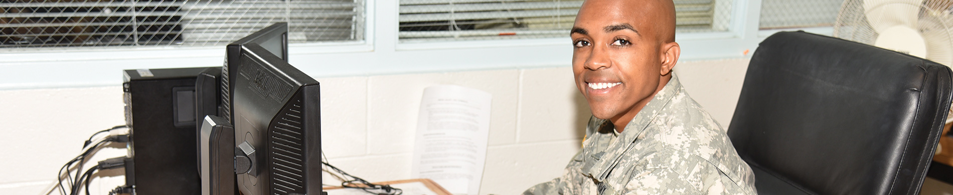 Student dressed in military fatigues sitting at computer