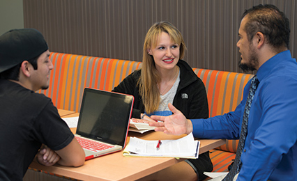 Advisor talking to two students while they work in a desk