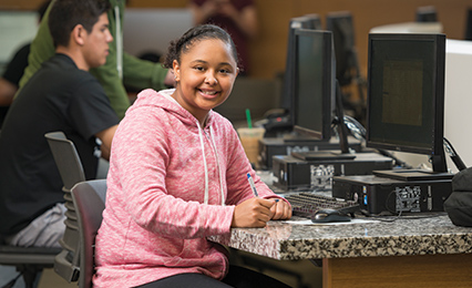 Young student in the Library building smiling at the camera