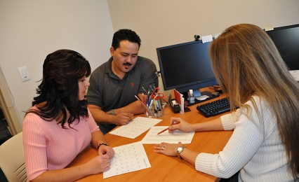 Advisor helping two adult learners with their application